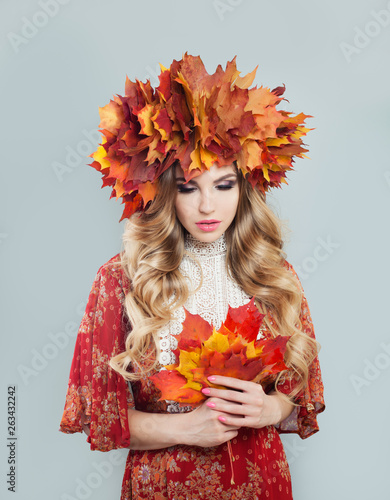 Nice autumn woman in fall leaves crown on gray background