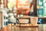 Hot coffee glass cup with glasses on wooden table in coffee shop. Vintage tone