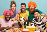 Cheerful five companions smile broadly, express positive emotions, exhilaration, observe sport game, hold football attribute laugh gladfully as favourite team wins opponent eat popcorn and drink beer