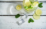 Mojito cocktail with slices of lime and mint leaves in highball glass on a wood table. White background.