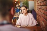 Gorgeous Caucasian brunette sitting in restaurant with her boyfriend and drinking coffee.