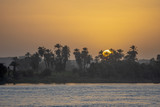 The Egyptian sun rises behind palm trees on the banks of the Upper Nile River in the Aswan Governorate, Egypt.