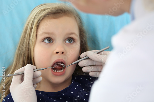 Zobacz obraz Little baby girl sitting at dental chair with open mouth and feeling fear during oral check up while doctor. Visiting dentist office. Medicine concept