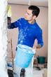 Male construction worker priming doorway