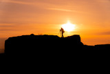 Silhouette of a photographer who shoots a sunset, on top of castle at sunset background.
