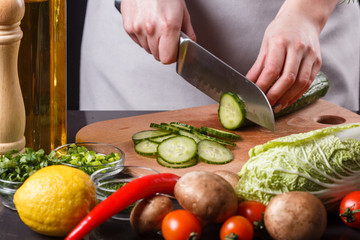 young woman in a gray apron cuts a cucumber