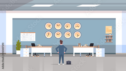 businessman looking on wall with clocks of different cities time management deadline concept modern workspace office interior horizontal rear view male character full length © mast3r