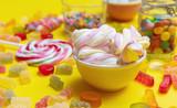 Fototapeta Kawa jest smaczna - Colorful candies assortment on yellow color background, closeup view © Rawf8