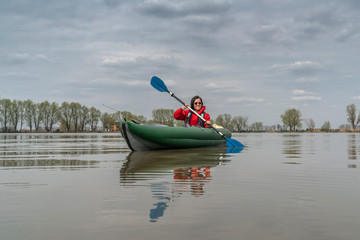 Kayak fishing at lake. Fisherwoman on inflateble boat with fishing tackle.
