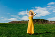 Beautiful girl in yellow dress and on mountain meadow with dandelions. - 263643647