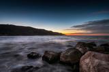 tramonto sul mare alla baia Flaminia di Pesaro con scogli in primo piano e collina sullo sfondo