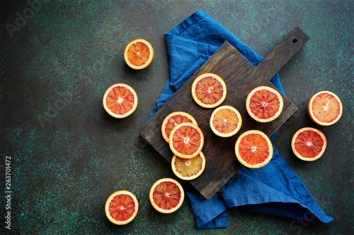 canvas print picture Red blood orange fruit on a dark green background. Oranges Slices. Healthy Food