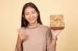Asian woman thumbs up with a gift box.