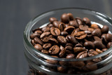 jar of coffee beans on a wooden background, concept photo, closeup