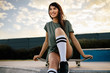 Attractive woman sitting on the skateboard at skate park