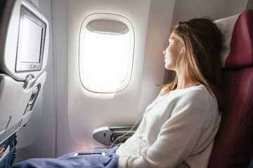 Teenage girl travelling by airplane