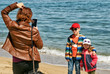 mom takes pictures of children smartphone on the sea coast