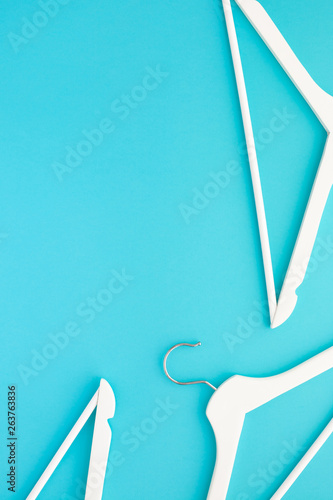White wooden hangers on blue background