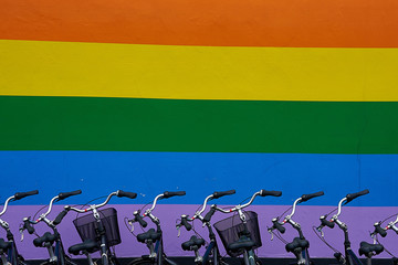 rainbow flag painted on wall. parked bikes © Mika