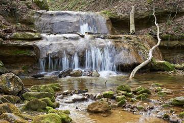 Dorfbach mit Wasserfall im Erlenbacher Tobel, verwischtes Wasser, Stufen, Wassertümpel, Aeste, Steine, Moos, grüne Blätter