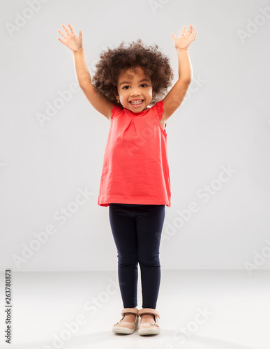 childhood and people concept - happy little african american girl with hands up over grey background © Syda Productions