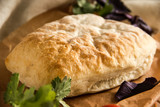 Ciabatta italian white bread on parchment paper on a wooden table, next to fresh greens and cotton napkin.