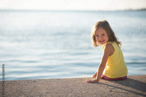 Portrait of smiling girl sitting near an ocean shore © Martinan
