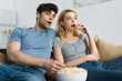 shocked man watching movie near blonde girl and bowl with popcorn