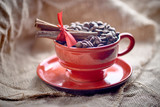 red cup with coffee beans and cinnamon sticks