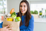 Young beautiful woman smiling holding a paper bag full of groceries at home