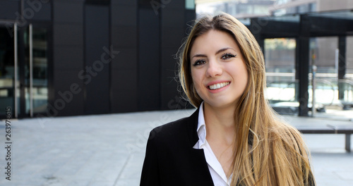 Confident young female manager walking outdoor in a modern urban setting © Minerva Studio