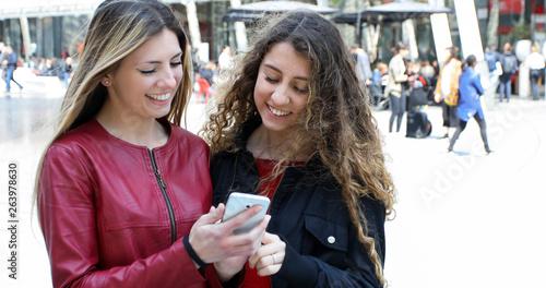 Two happy women friends looking at a smartphone outdoor © Minerva Studio