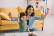 excited mother and son with color pencils waving hands in living room