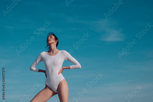 Adorable beauty. Classic dance style. Young ballerina dancing on blue sky. Cute ballet dancer. Pretty girl in dance wear. Practicing art of classical ballet. Concert performance dance, copy space © tverdohlib