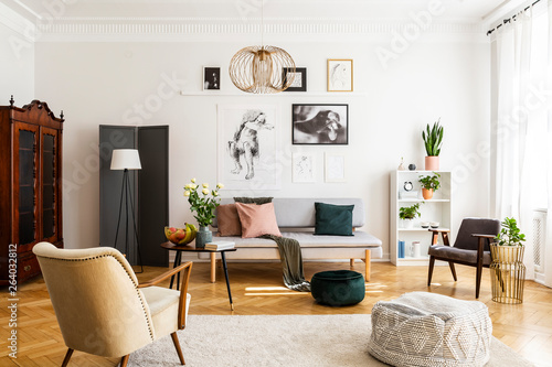 Retro beige armchair and pouf on the cozy carpet in contemporary living room interior with grey sofa and vintage furniture