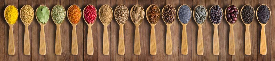 Colorful spices on background wooden table. Seasonings and herbs in wooden spoons for design website headers. © dmitr1ch