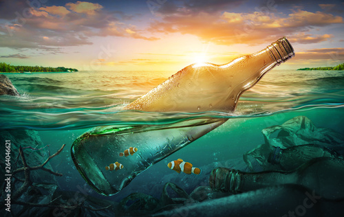 Small fishes in a bottle among ocean pollution. Environment concept © chaiyapruek
