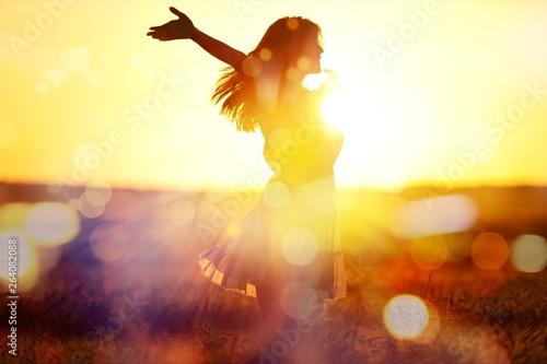 Young woman on field under sunset light © BillionPhotos.com