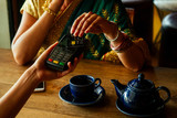 Young indian businesswoman in green traditional sari on a coffee break. Using payment terminal paying by credit card in a cafe restaurant.black friday sale