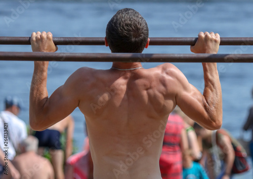 A man pulls himself up on a horizontal bar in the park © schankz