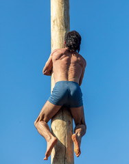 A man climbs a wooden pole against the blue sky