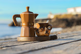 Breakfast on the beach for two. Coffee maker with cups and French croissants. Romantic date background.