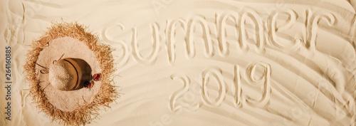 panoramic shot of summer 2019 written on wavy sand with straw hat © LIGHTFIELD STUDIOS