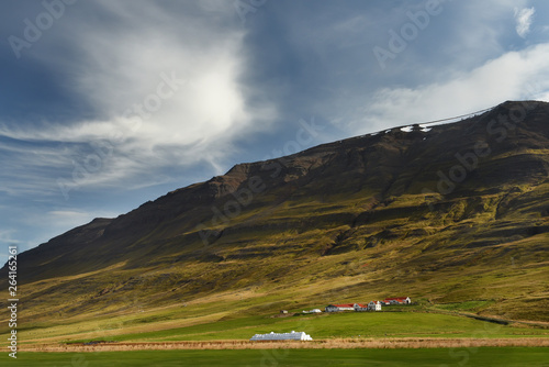 Small houses in the valley among the mountains. Typical Icelandic landscape. A beautiful view of secluded housing.