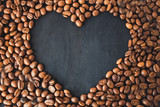 Coffee beans in the form of a heart on a black wooden background. Coffee heart