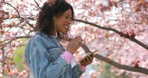 Multiracial woman listening to music puts on wire earphones in a park at springtime, cherry blossoms tree around