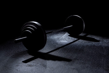 365 pound weights in gym on barbell with dramatic lighting