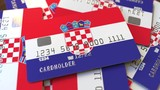 Pile of credit cards with flag of Croatia. Croatian banking system conceptual 3D animation