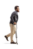 Young bearded man walking with crutches