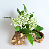 Bouquet of lily of the valley is placed in bast like as in a vase on a white background